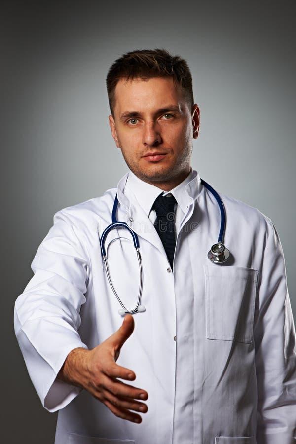 Medico con lo stetoscopio che dà mano per handshake immagine stock