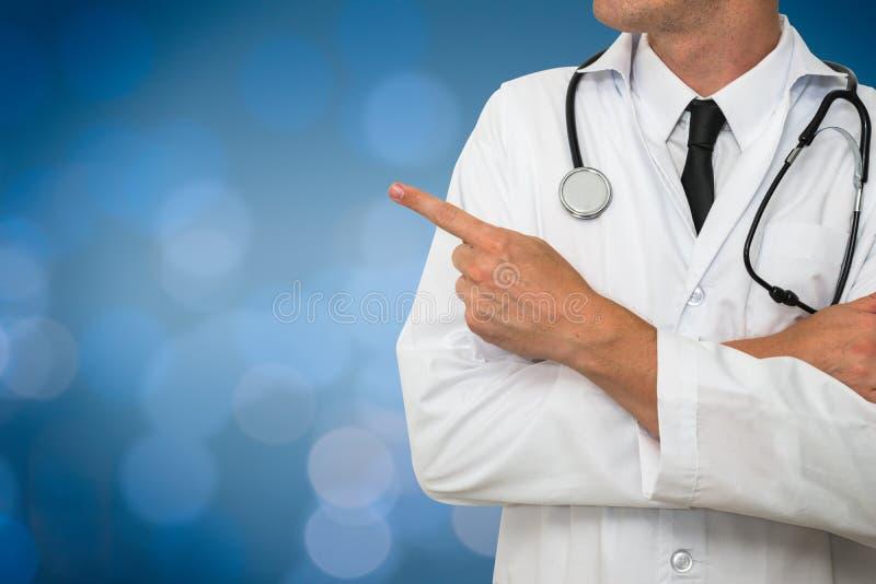 Medico con lo stetoscopio che mostra uno spazio in bianco su fondo medico blu immagini stock libere da diritti