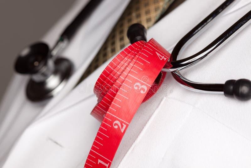 Medico con lo stetoscopio e nastro adesivo di misurazione fotografie stock