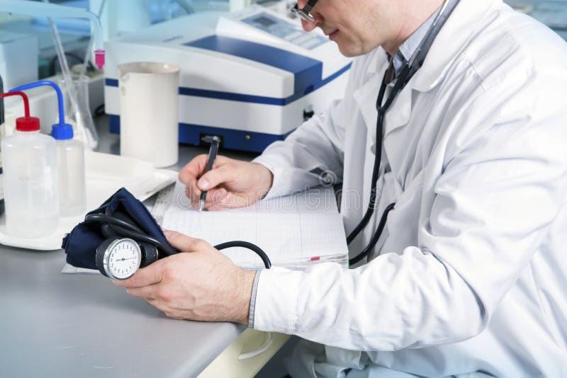 Medico con lo stetoscopio, i vetri e l'abito scrivono sulla tavola fotografia stock