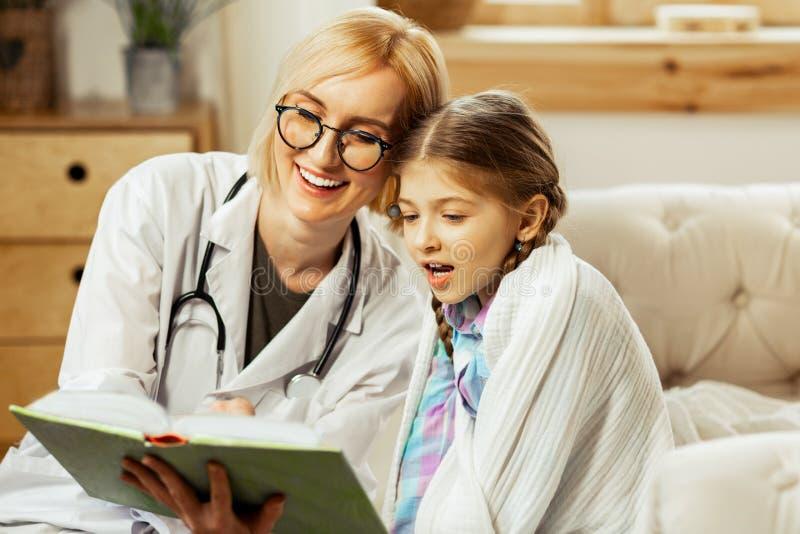 Medico d'orientamento che gode di una lettura del libro con una ragazza fotografia stock