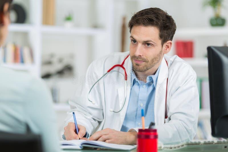 Medico medico del medico che ascolta il paziente e che prende le note fotografia stock