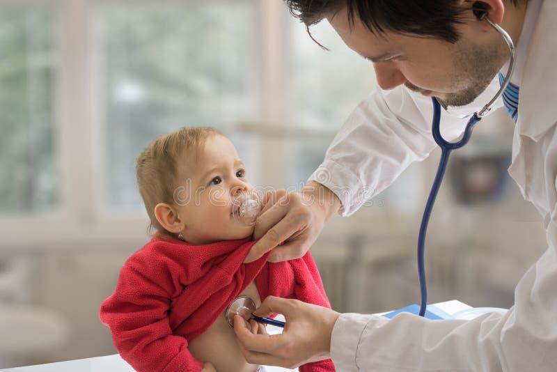 Medico del pediatra sta esaminando il bambino con lo stetoscopio immagine stock libera da diritti