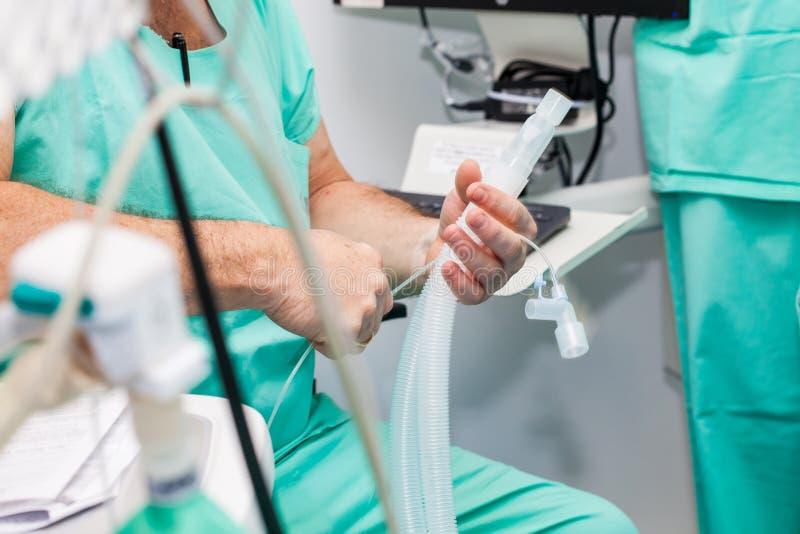Medico dell'anestesista che si prepara per dare anestesia al paziente nella stanza della chirurgia immagine stock