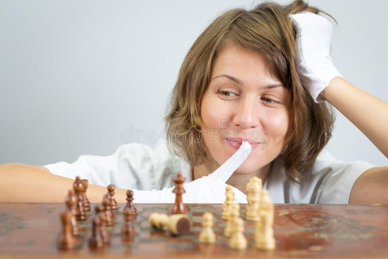 Medico dell'infermiere della giovane donna che gioca gli scacchi dà scacco matto i pezzi ritenenti del gioco fotografia stock