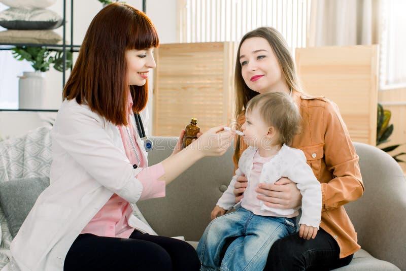 Medico della donna che dà a dose del cucchiaio dello sciroppo bevente del liquido della medicina alla neonata del bambino il suo  immagine stock libera da diritti