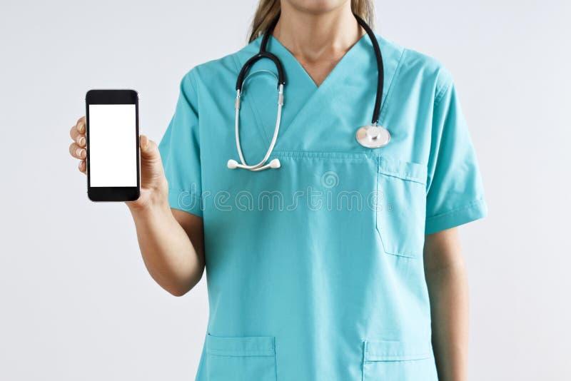 Medico della donna che mostra lo schermo del telefono cellulare isolato su un fondo grigio immagine stock