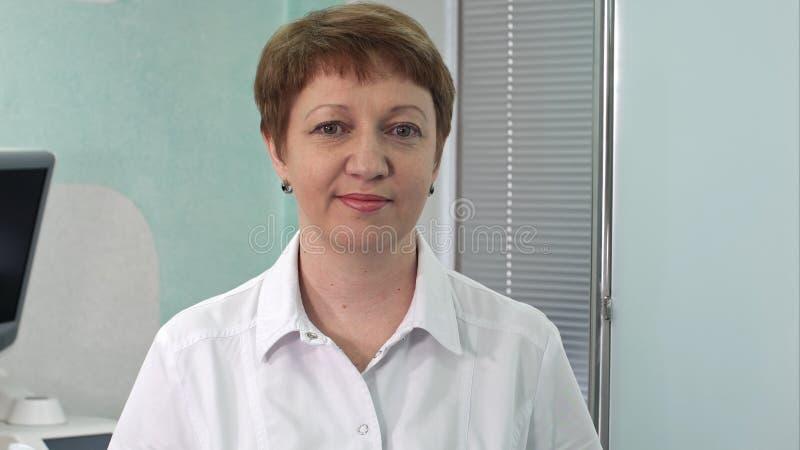 Medico della donna che sorride e che guarda alla macchina fotografica fotografia stock libera da diritti