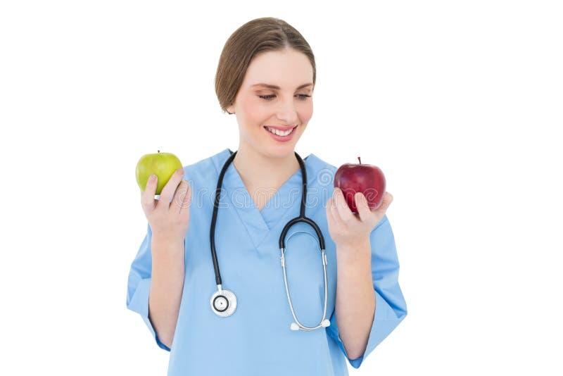 Medico della giovane donna che tiene due mele fotografia stock libera da diritti