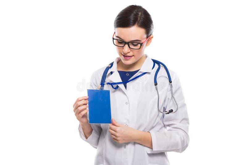 Medico della giovane donna con il distintivo della tenuta dello stetoscopio in sue mani ed esaminare il suo distintivo in uniform immagini stock libere da diritti