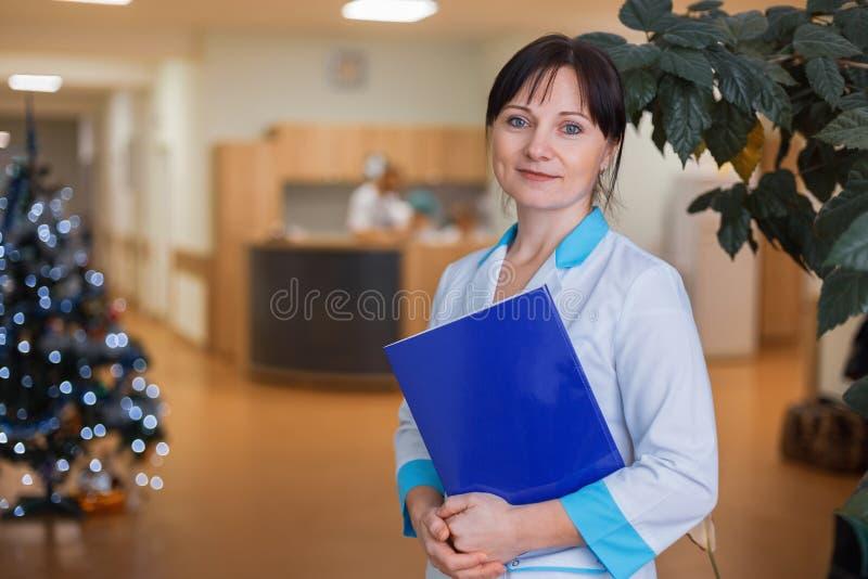 Medico delle donne in un abito medico sta tenendo una cartella blu per i documenti nel corridoio dell'ospedale fotografia stock
