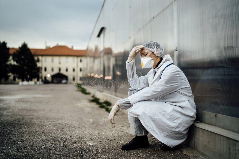 Medico depresso in lacrime con maschera con esaurimento mentale Paura, ansia, panico per l'epidemia di coronavirus Psicologico fotografia stock