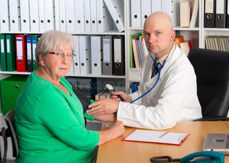 Medico di famiglia esamina un anziano femminile fotografie stock