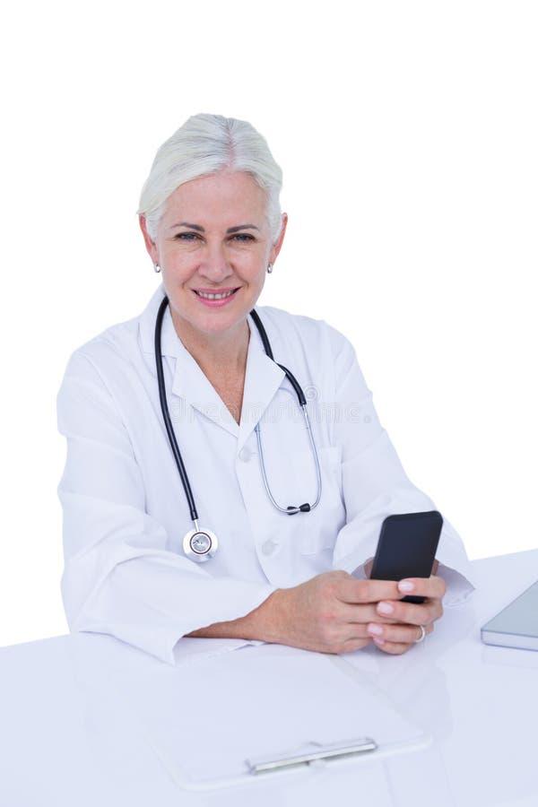 Medico di pensiero della donna che telefona con il suo smartphone fotografia stock libera da diritti