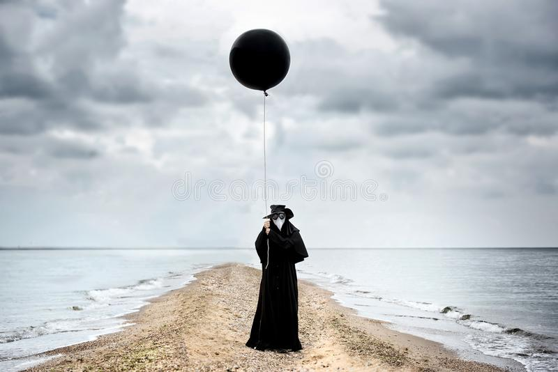 Medico di peste con il pallone nero in spiaggia fotografia stock libera da diritti