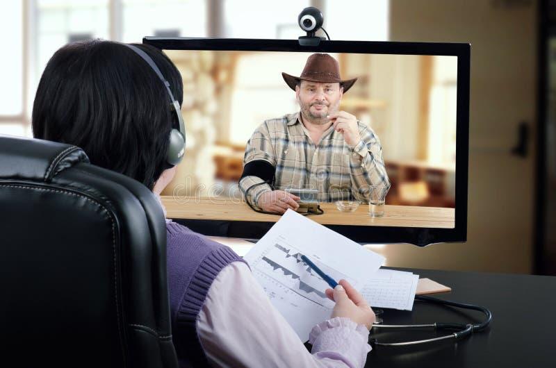 Medico di Telehealth esamina il grafico di pressione sanguigna dell'uomo del paese fotografie stock