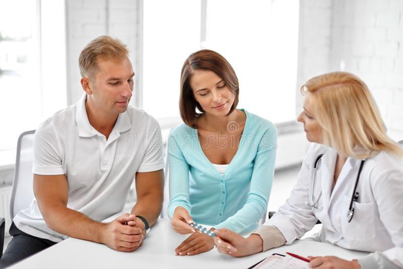 Medico di visita delle coppie alla clinica di pianificazione familiare fotografia stock