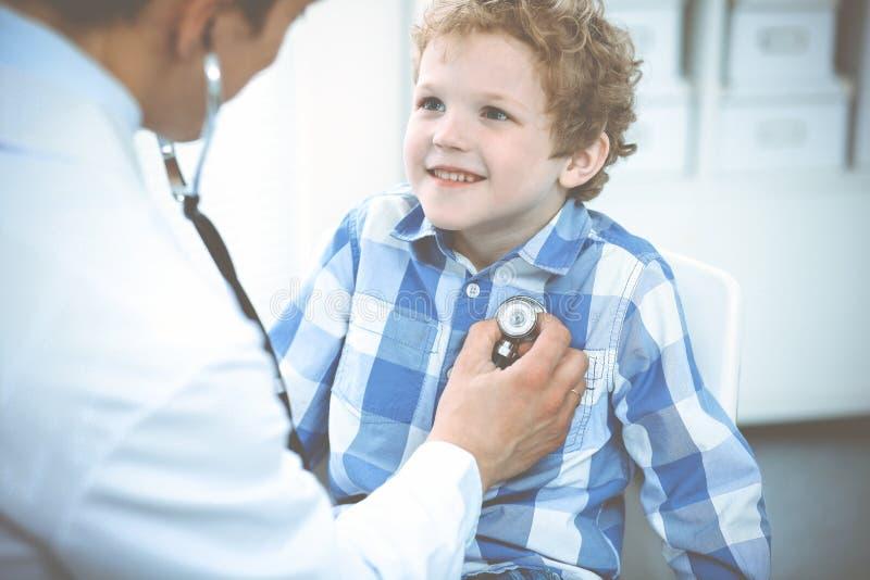 Medico e bambino paziente Ragazzino d'esame del medico Visita medica regolare in clinica Medicina e sanit? immagini stock
