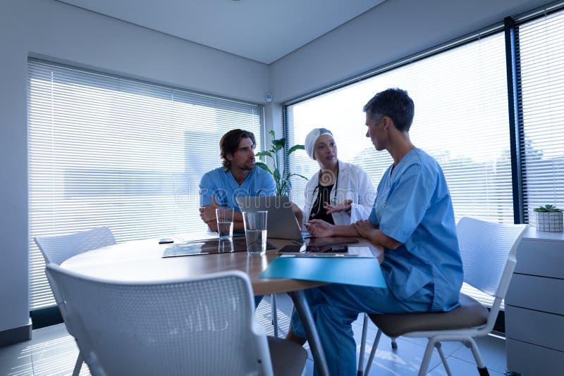 Medico e chirurgo che discutono sopra il computer portatile nella clinica all'ospedale fotografia stock