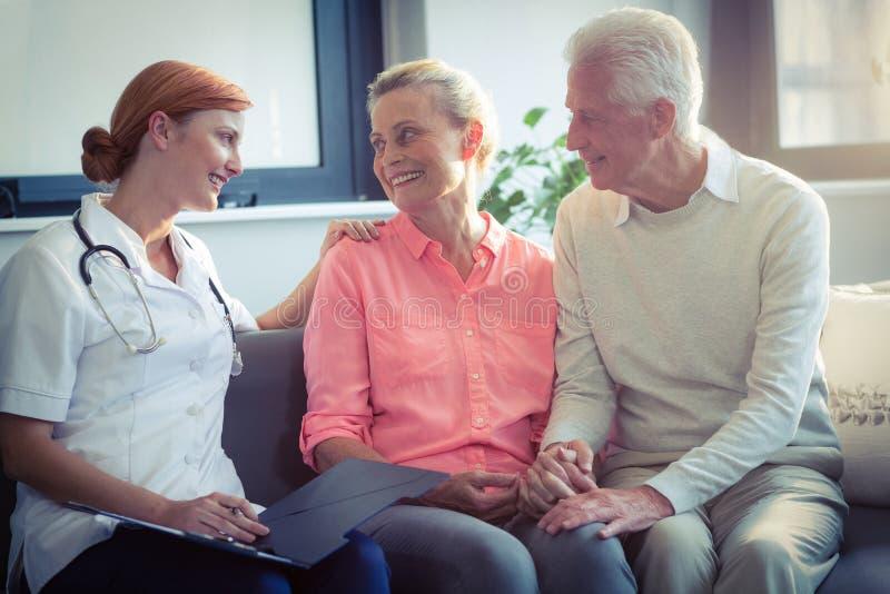 Medico e coppie senior che interagiscono a vicenda immagine stock libera da diritti