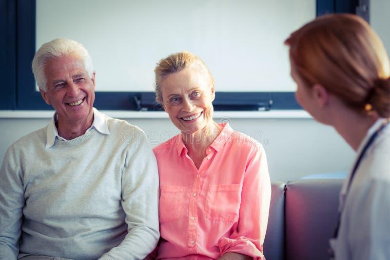Medico e coppie senior che interagiscono a vicenda fotografie stock libere da diritti