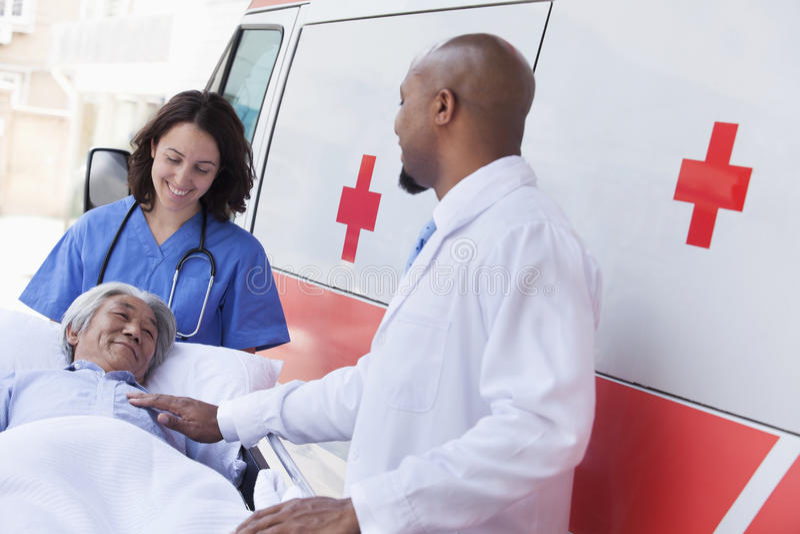 Medico e paramedico che spingono in un paziente anziano su una barella davanti ad un'ambulanza immagine stock libera da diritti
