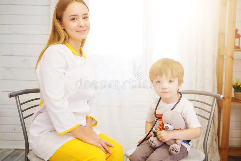 Medico e paziente a casa La bambina sta esaminanda dal pediatra con lo stetoscopio Medicina e sanità fotografie stock libere da diritti