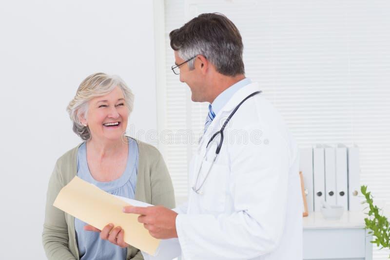 Medico e paziente che conversano sopra i rapporti fotografie stock libere da diritti