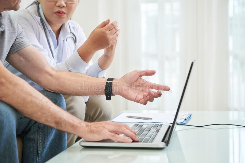 Medico e paziente che discutono i risultati delle prove immagini stock libere da diritti
