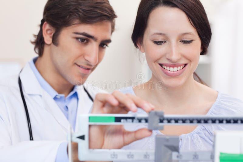 Medico e paziente che regolano insieme la scala immagini stock libere da diritti
