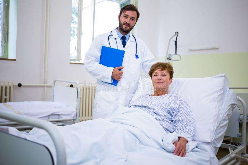 Medico e paziente sorridenti che esaminano macchina fotografica in ospedale fotografia stock