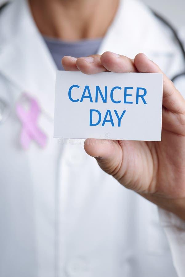 Medico ed insegna con il giorno del cancro del testo fotografia stock