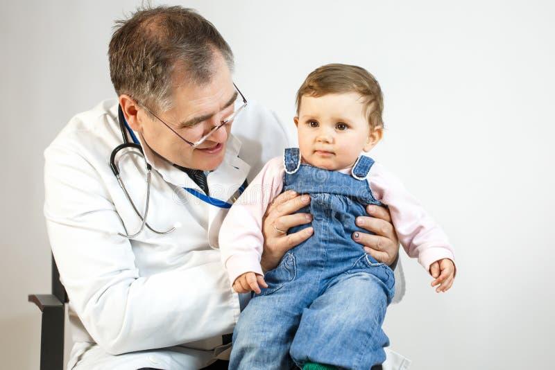 Medico esamina il bambino che lo tiene nelle sue armi immagini stock