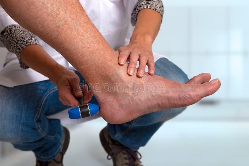 Medico esamina il riflesso del tendine di Achille con il martello riflesso fotografia stock