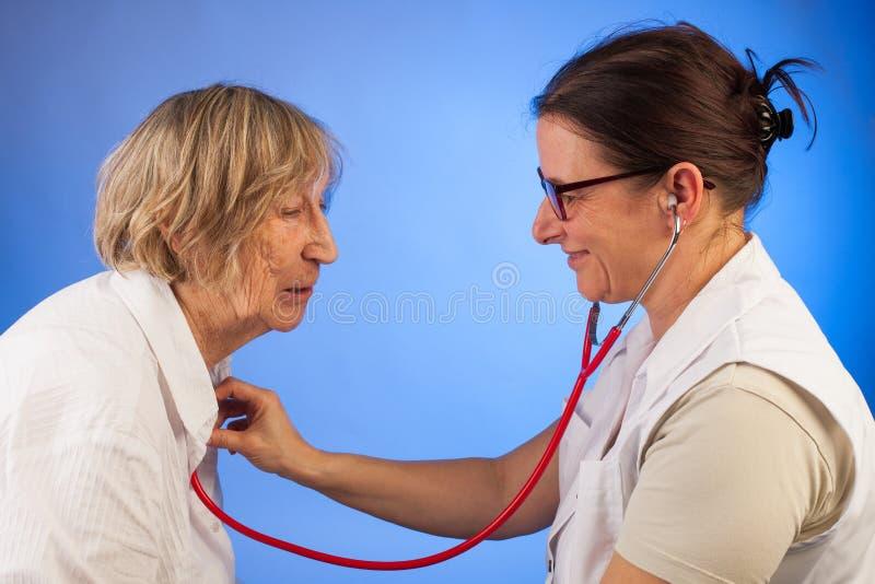 Medico esamina la donna senior con uno stetoscopio fotografie stock libere da diritti