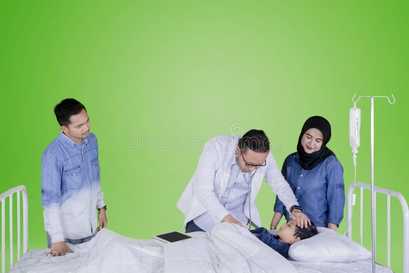 Medico esamina un ragazzino nello studio fotografia stock libera da diritti