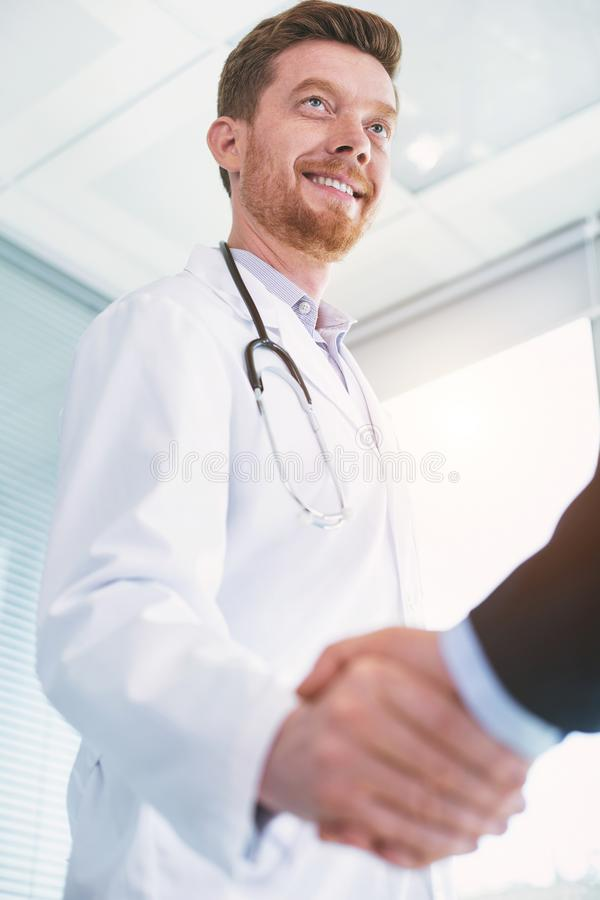 Medico esuberante che stringe le mani con un uomo d'affari fotografia stock