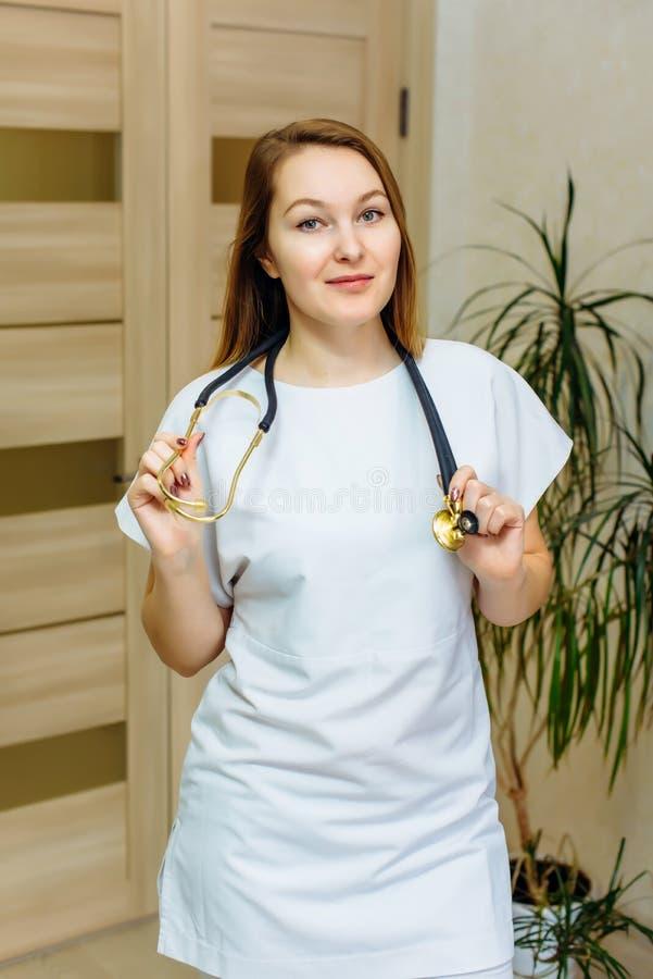Medico europeo sorridente della donna con lo stetoscopio in un'uniforme bianca Ritratto di giovane lavoratore medico con l'attegg fotografie stock libere da diritti