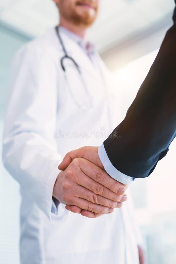Medico felice che stringe le mani con un uomo d'affari fotografie stock