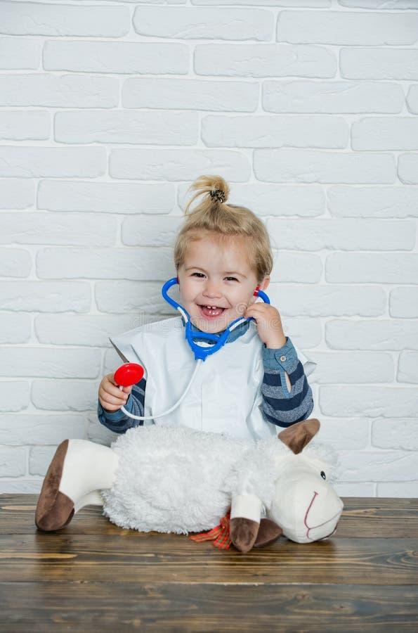 Medico felice del gioco da bambini con le pecore del giocattolo sulla parete bianca fotografia stock libera da diritti