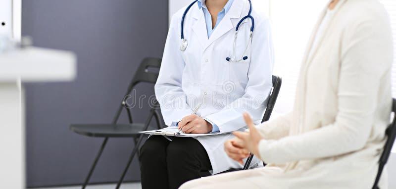 Medico felice e paziente che discutono qualcosa mentre sedendosi alle sedie all'ospedale Medico sul lavoro in clinica immagini stock libere da diritti