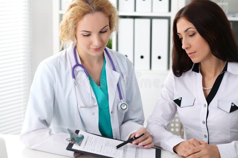 Medico felice e paziente femminili biondi che discutono i risultati dell'esame medico Concetto della medicina, di sanità e di aiu immagini stock libere da diritti