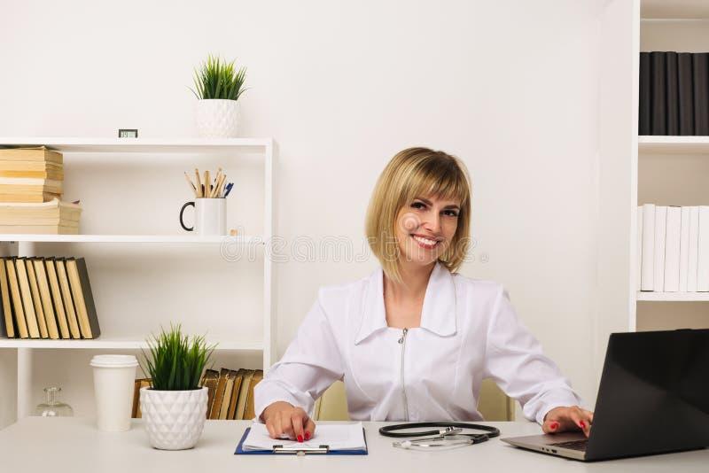 Medico femminile amichevole lavora al suo scrittorio nell'ufficio fotografia stock