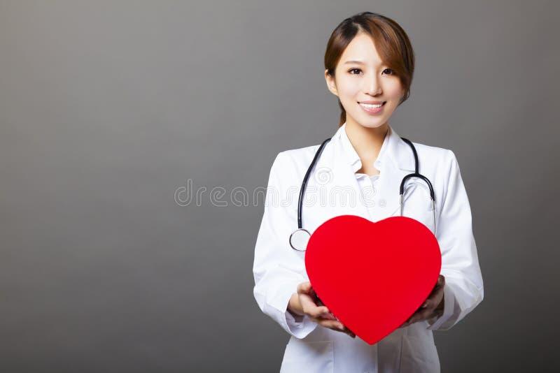 Medico femminile asiatico con cuore fotografie stock libere da diritti
