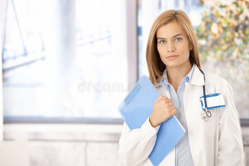 Medico femminile attraente che si leva in piedi nell'ufficio fotografia stock libera da diritti