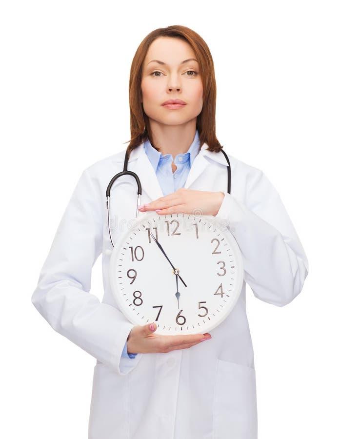Medico femminile calmo con l'orologio di parete fotografia stock libera da diritti