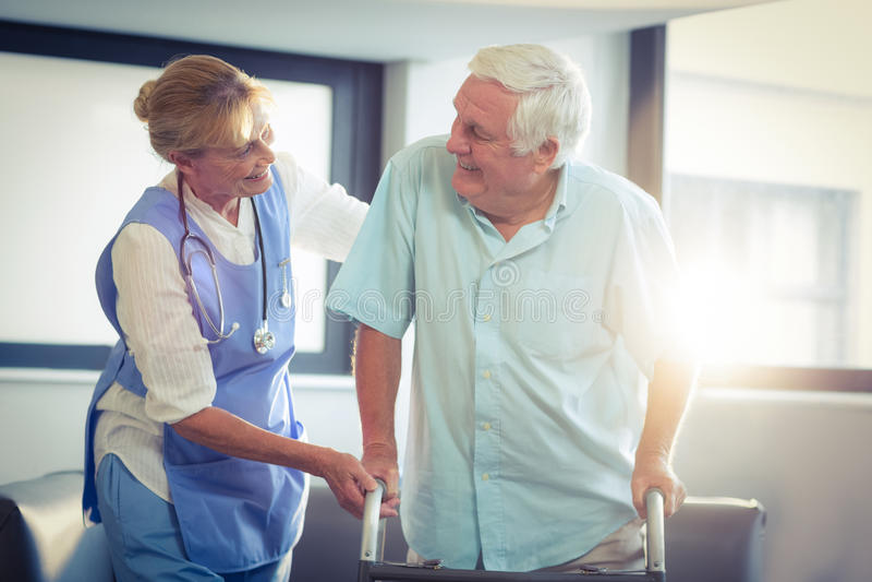 Medico femminile che aiuta uomo senior a camminare con il camminatore immagine stock