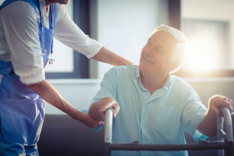 Medico femminile che aiuta uomo senior a camminare con il camminatore fotografia stock