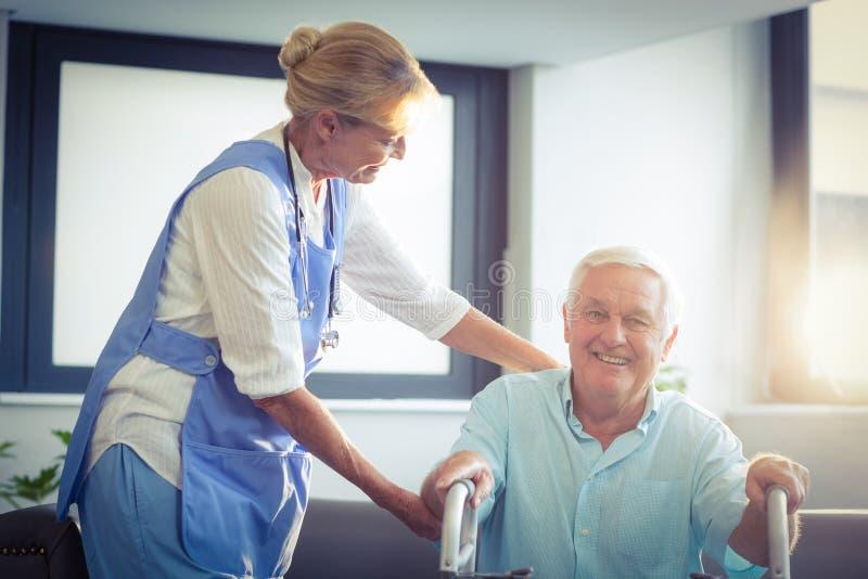 Medico femminile che aiuta uomo senior a camminare con il camminatore immagine stock libera da diritti