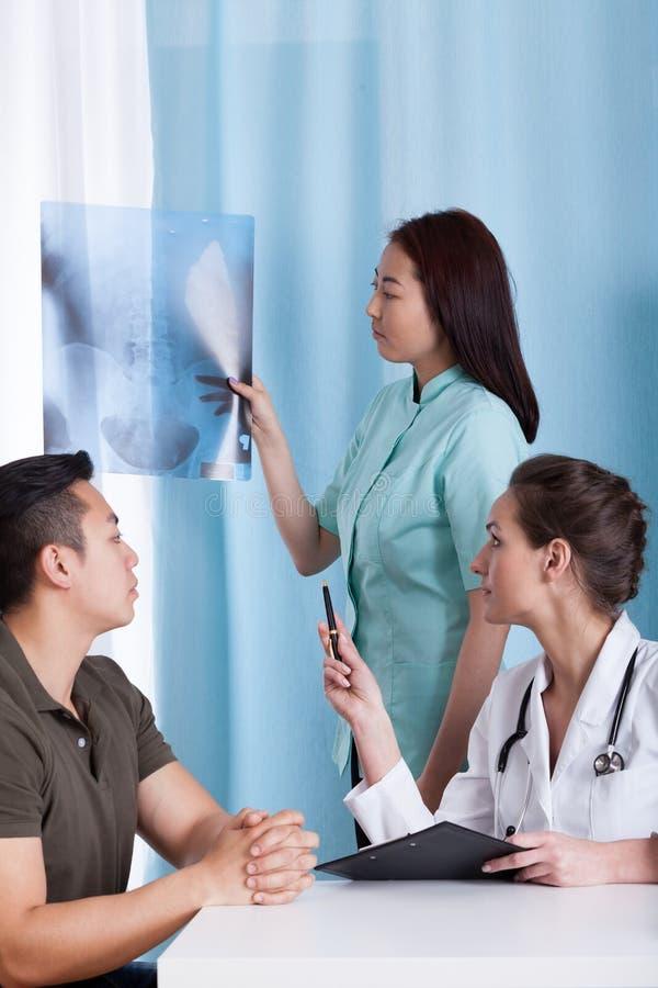 Medico femminile che analizza raggi x del suo paziente asiatico immagini stock